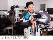 Купить «Man in moto jacket is choosing new helmet for motorbike in the store.», фото № 29734893, снято 1 сентября 2017 г. (c) Яков Филимонов / Фотобанк Лори