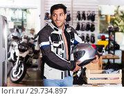 Купить «Man in moto equipment store», фото № 29734897, снято 1 сентября 2017 г. (c) Яков Филимонов / Фотобанк Лори