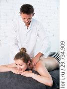 Купить «male masseur doing massage at back young woman who lying on a massage table in a beauty salon», фото № 29734909, снято 12 июня 2017 г. (c) Яков Филимонов / Фотобанк Лори