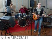 Купить «Expressive guitar player and singer with band», фото № 29735121, снято 26 октября 2018 г. (c) Яков Филимонов / Фотобанк Лори