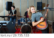 Купить «Attractive female soloist playing guitar and singing with her music band in sound studio», фото № 29735133, снято 26 октября 2018 г. (c) Яков Филимонов / Фотобанк Лори