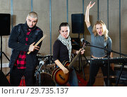 Купить «Three bandmates posing together with musical instruments in rehearsal room», фото № 29735137, снято 26 октября 2018 г. (c) Яков Филимонов / Фотобанк Лори
