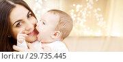 Купить «close up of mother with baby over christmas lights», фото № 29735445, снято 22 декабря 2007 г. (c) Syda Productions / Фотобанк Лори