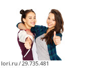 Купить «happy teenage girls hugging and showing thumbs up», фото № 29735481, снято 19 декабря 2015 г. (c) Syda Productions / Фотобанк Лори