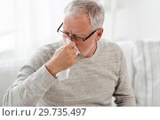 sick senior man with paper wipe blowing his nose. Стоковое фото, фотограф Syda Productions / Фотобанк Лори