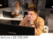 tired or bored man with computer at night office. Стоковое фото, фотограф Syda Productions / Фотобанк Лори