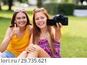 Купить «teenage bloggers recording video by camera in park», фото № 29735621, снято 19 июля 2018 г. (c) Syda Productions / Фотобанк Лори