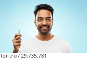 Купить «indian man with toothbrush over blue background», фото № 29735781, снято 27 октября 2018 г. (c) Syda Productions / Фотобанк Лори