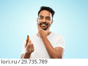 smiling indian man applying grooming oil to beard. Стоковое фото, фотограф Syda Productions / Фотобанк Лори