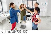 Купить «happy creative team making high five at office», фото № 29735937, снято 1 апреля 2018 г. (c) Syda Productions / Фотобанк Лори