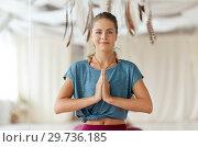 woman with namaste gesture at yoga studio. Стоковое фото, фотограф Syda Productions / Фотобанк Лори