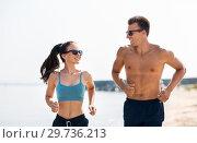 Купить «couple in sports clothes running along on beach», фото № 29736213, снято 1 августа 2018 г. (c) Syda Productions / Фотобанк Лори