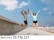 Купить «happy couple in sports clothes jumping on pier», фото № 29736221, снято 1 августа 2018 г. (c) Syda Productions / Фотобанк Лори