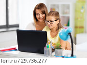 mother and daughter with laptop doing homework. Стоковое фото, фотограф Syda Productions / Фотобанк Лори