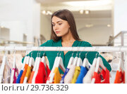Купить «woman choosing clothes at clothing store», фото № 29736329, снято 19 февраля 2016 г. (c) Syda Productions / Фотобанк Лори