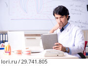 Купить «Young handsome dentist in front of the whiteboard», фото № 29741805, снято 15 октября 2018 г. (c) Elnur / Фотобанк Лори