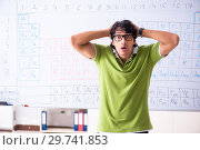 Купить «Young male student chemist in front of periodic table», фото № 29741853, снято 19 октября 2018 г. (c) Elnur / Фотобанк Лори