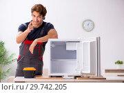 Купить «Young handsome contractor repairing fridge», фото № 29742205, снято 5 октября 2018 г. (c) Elnur / Фотобанк Лори
