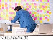 Купить «Young handsome employee with many conflicting priorities», фото № 29742781, снято 16 октября 2018 г. (c) Elnur / Фотобанк Лори