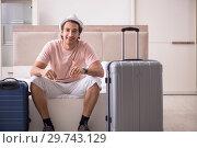 Купить «Man with suitcase in bedroom waiting for trip», фото № 29743129, снято 17 сентября 2018 г. (c) Elnur / Фотобанк Лори