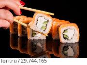Купить «Японская кухня. Суши ролл. Фото для меню азиатская кухня. Роллы с лососем держит в руке на палочках девушка с красными ноглями.», фото № 29744165, снято 19 января 2018 г. (c) Евгений Бобков / Фотобанк Лори