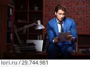Купить «Young businessman working in the office at night», фото № 29744981, снято 28 августа 2018 г. (c) Elnur / Фотобанк Лори