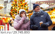Купить «senior couple with hot drinks at christmas market», видеоролик № 29745893, снято 10 января 2019 г. (c) Syda Productions / Фотобанк Лори
