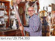 Купить «Smiling man carefully examining antiques», фото № 29754393, снято 15 мая 2018 г. (c) Яков Филимонов / Фотобанк Лори