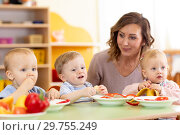 Купить «Babies and carer together eat fruits and vegetables as a snack in the kindergarten, nursery or daycare», фото № 29755249, снято 27 мая 2020 г. (c) Оксана Кузьмина / Фотобанк Лори