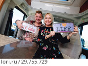 Купить «Cheerful laughing middle age family positive travelers couple sitting inside of camper holds hippy retro styled number plate or license number with text This the season to be married and I love life», фото № 29755729, снято 11 ноября 2018 г. (c) Alexander Tihonovs / Фотобанк Лори
