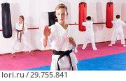 Купить «Preteen boy practicing karate movements with male trainer supervision», фото № 29755841, снято 3 июля 2020 г. (c) Яков Филимонов / Фотобанк Лори