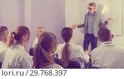 Купить «Positive male teacher lecturing to students», фото № 29768397, снято 5 октября 2017 г. (c) Яков Филимонов / Фотобанк Лори