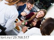 Купить «Smiling company are dinnering in luxury restaurante alone», фото № 29768517, снято 18 декабря 2017 г. (c) Яков Филимонов / Фотобанк Лори