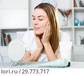 Купить «Cheerful woman is concentrared looking on her face in the mirror», фото № 29773717, снято 29 марта 2018 г. (c) Яков Филимонов / Фотобанк Лори