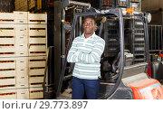 Купить «African American man standing near forklift at fruit warehouse», фото № 29773897, снято 15 декабря 2018 г. (c) Яков Филимонов / Фотобанк Лори