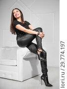 Купить «Young pretty brunette posing sitting.», фото № 29774197, снято 26 апреля 2016 г. (c) Сергей Сухоруков / Фотобанк Лори