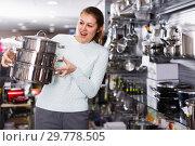 Купить «cheerful woman is looking modern saucepan in the store», фото № 29778505, снято 5 февраля 2018 г. (c) Яков Филимонов / Фотобанк Лори