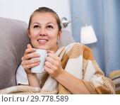 Купить «Young female is warming with tea and sitting in plaide», фото № 29778589, снято 19 марта 2019 г. (c) Яков Филимонов / Фотобанк Лори