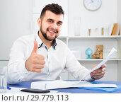 Купить «Smiling young man signing profitable financial agreement», фото № 29779113, снято 5 марта 2017 г. (c) Яков Филимонов / Фотобанк Лори