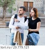 Купить «Happy young family of tourists with map and baggage», фото № 29779121, снято 25 мая 2017 г. (c) Яков Филимонов / Фотобанк Лори