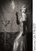 Купить «Girl in an evening dress with a cigarette mouthpiece. Studio portrait in retro style, toned in sepia», фото № 29779577, снято 27 декабря 2018 г. (c) Вадим Орлов / Фотобанк Лори