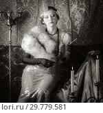 Купить «Girl in an evening dress with a cigarette mouthpiece. Studio portrait in retro style, toned in sepia», фото № 29779581, снято 27 декабря 2018 г. (c) Вадим Орлов / Фотобанк Лори