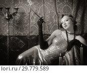 Купить «Girl in an evening dress with a cigarette mouthpiece. Studio portrait in retro style, toned in sepia», фото № 29779589, снято 27 декабря 2018 г. (c) Вадим Орлов / Фотобанк Лори