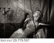 Купить «Girl in an evening dress with a cigarette mouthpiece. Studio portrait in retro style, toned in sepia», фото № 29779597, снято 27 декабря 2018 г. (c) Вадим Орлов / Фотобанк Лори