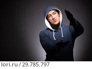 Купить «Young gangster in hood on grey background», фото № 29785797, снято 27 сентября 2018 г. (c) Elnur / Фотобанк Лори