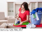 Купить «Young beautiful woman ironing at home», фото № 29786357, снято 30 октября 2018 г. (c) Elnur / Фотобанк Лори
