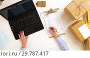 Купить «woman with laptop and clipboard at post office», видеоролик № 29787417, снято 19 января 2019 г. (c) Syda Productions / Фотобанк Лори