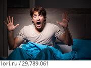 Купить «Young man scared in his bed having nightmares», фото № 29789061, снято 18 сентября 2018 г. (c) Elnur / Фотобанк Лори