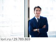 Купить «Young handsome businessman standing at the window», фото № 29789869, снято 2 августа 2018 г. (c) Elnur / Фотобанк Лори