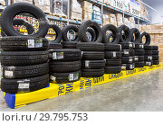 Brand new tires stacked up for sale in the chain hypermarket (2018 год). Редакционное фото, фотограф FotograFF / Фотобанк Лори